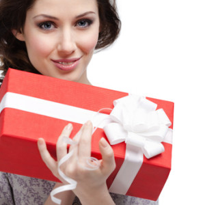Young woman holds a gift wrapped in red paper, isolated on white
